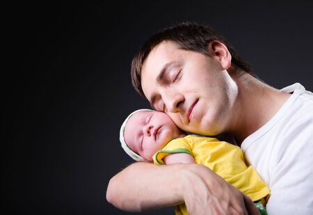 Studio picture of happy young father with his 14 days old newborn daughter over black background Stock Photo - 3371781