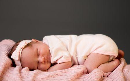 infancy: Sleeping Beauty. Studio photo of 14 days old newborn baby girl sleeping on blanket Stock Photo