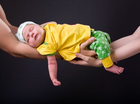 Supporting Hands. Parents holding 14 days old baby girl on theirs arms photo