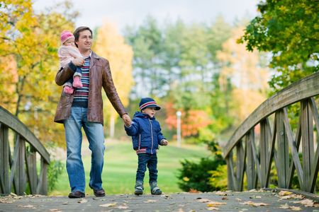Young father with two kids enjoying beautiful autumn day photo