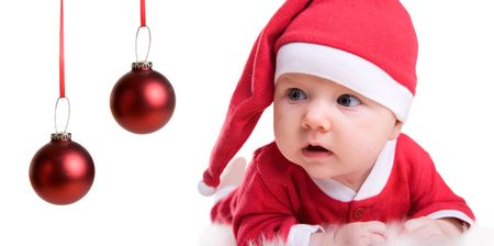 Portrait of Christmas baby girl in red Santa hat