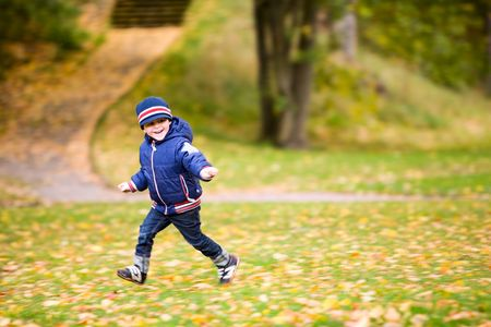4-years old boy playing and running in beautiful autumnal park  photo