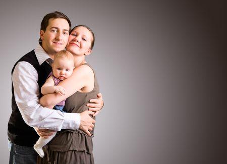 papa y mama: Estudio de la imagen feliz de los padres j�venes y 4 meses de edad, m�s de ni�a fondo gris oscuro