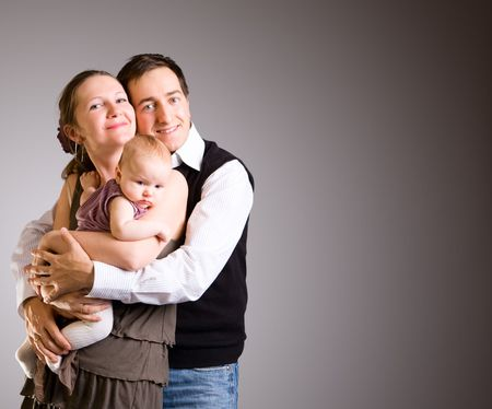 Studio picture of happy young parents and 4 months old baby girl over dark gray background Stock Photo - 3804776