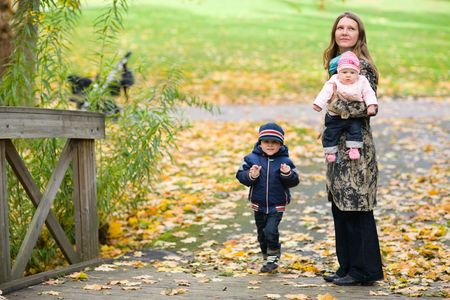 Young mother with two kids enjoying beautiful autumn day photo