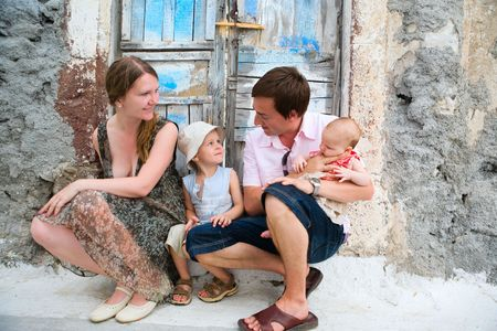 Happy young family of four sitting outdoors near old blue door. photo