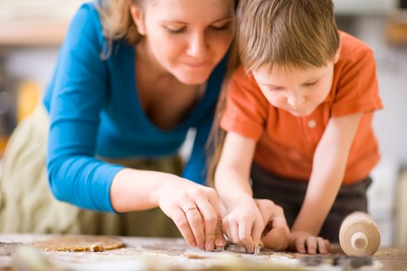 mom son: Young mother and son in kitchen making cookies.