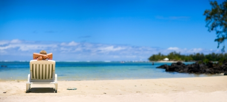 flip flops on the beach: Young woman relaxing on tropical white sand beach. Stock Photo