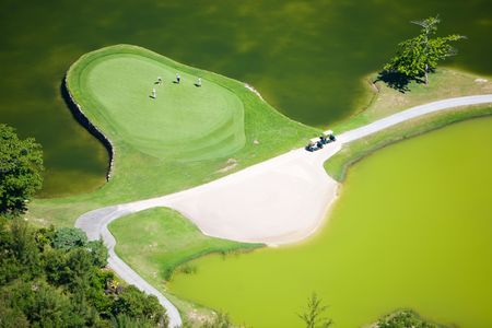 Aerial view of golf course in luxury resort in Mauritius. Four people playing golf. photo