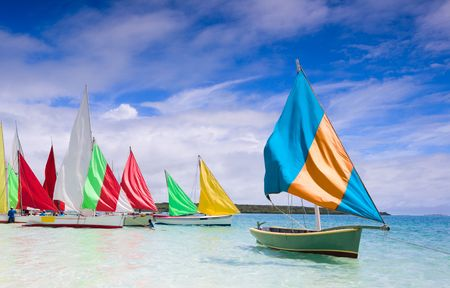 Preparation for start of a sailing regatta in Mauritius. Colorful traditional Mauritian wooden boats called Pirogue.