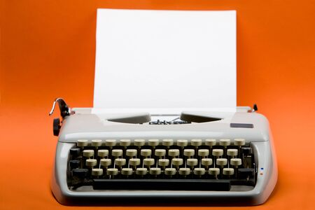 typewriter key: Old style typewriter with inserted blank paper over orange background Stock Photo