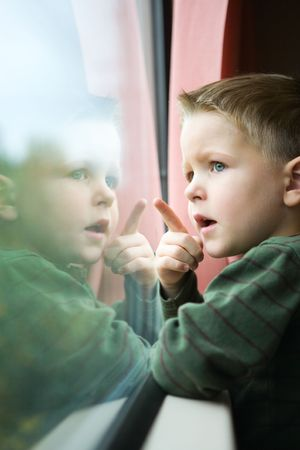 fast train: Cute 4-years old boy traveling by train Stock Photo