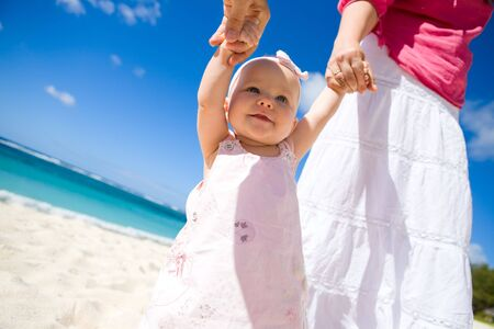 Young family with baby girl on white sand tropical beach photo