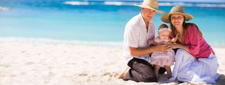 Family vacation. Young family of three on white sand tropical beach Stock Photo - 4224251