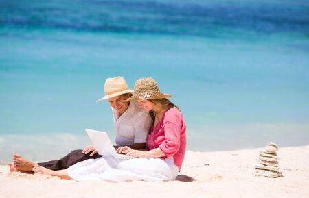 Looking for perfect vacation. Happy couple using laptop on the beach. photo