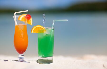 Two tropical cocktails on white sand beach photo