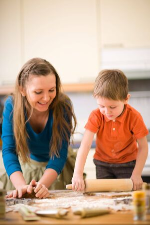 Young mother and son in kitchen making cookies. Focus on hands. photo