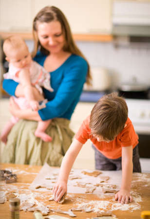 Young family in kitchen making gingerbread cookies. photo