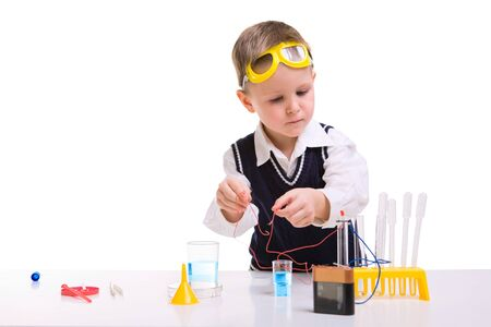 science scientific: Young boy performing experiments with battery and small lamp. Stock Photo