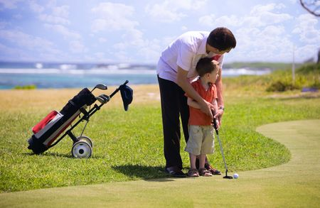 play golf: Father teaching his son how to play golf. Stock Photo