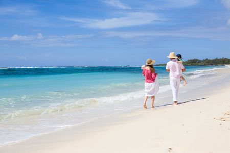 Family vacation. Young family of four walking along white sand tropical beach Stock Photo - 4377531