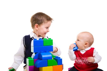 Brother and sister playing together with building blocks photo