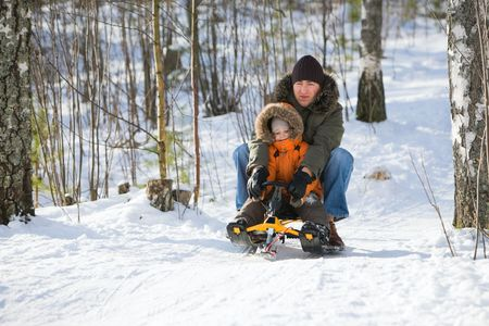 sledging people: Winter weekend. Father and son sledging on beautiful winter day. Stock Photo
