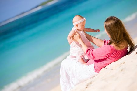 Young mother and baby girl on white sand tropical beach photo