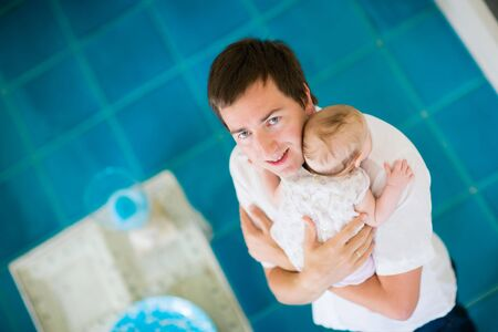 Happy young father and his baby daughter at home photo