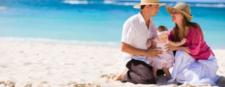 Family vacation. Panoramic photo of young family of three on white sand tropical beach Stock Photo - 4476959