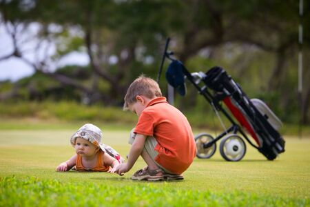 Two adorable kids playing on golf field waiting. photo