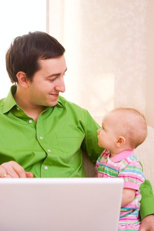 babysitting: Father working on laptop from home while babysitting his daughter