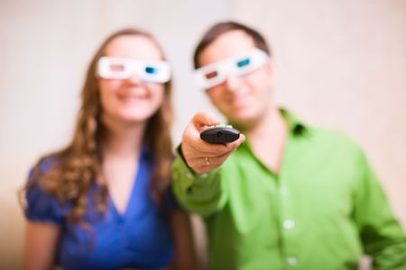Young couple at home watching movie in 3D glasses. Focus on remote control.  photo