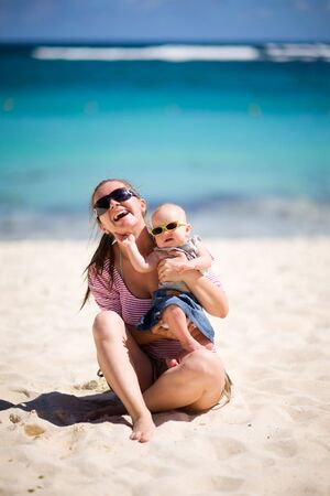 Young mother and baby girl in sunglasses on white sand tropical beach Stock Photo - 4577554