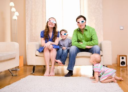 family movies: Happy family of four at home watching movie in 3D glasses.