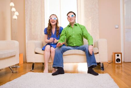 Happy couple at home watching movie in 3D glasses. photo
