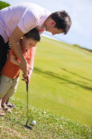 Father teaching his son how to play golf photo