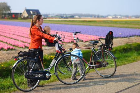 Family with two kids bicycling in dutch countryside. Tulip fields on background photo