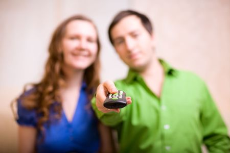 Young couple at home watching TV. Focus on remote control.  photo
