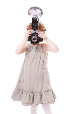 Young Photographer. Little girl playing with antique camera.  photo