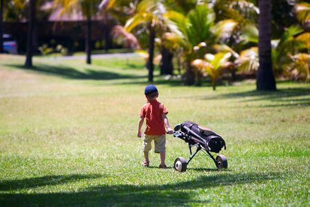 4 years old boy walking with golf bag photo