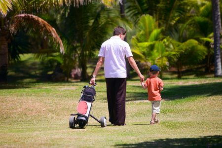 golfing: Father teaching his son to play golf.