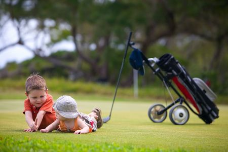 golf equipment: Two adorable kids playing on golf field waiting. Stock Photo