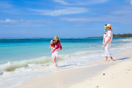 Family vacation. Young family of four on white sand tropical beach Stock Photo - 4918763