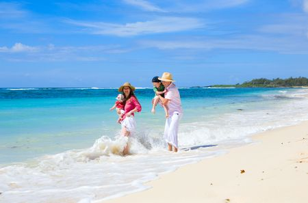Family vacation. Young family of four on white sand tropical beach Stock Photo - 4918759