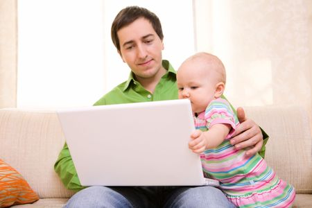 Father working on laptop from home while babysitting his daughter photo