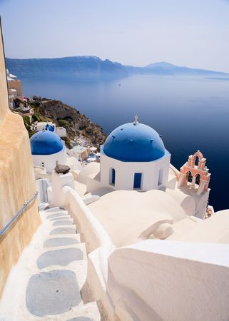 surrounding: Blue domed church in Oia overlooks the spectacular caldera surrounding the beautiful island of Santorini, Greece Stock Photo