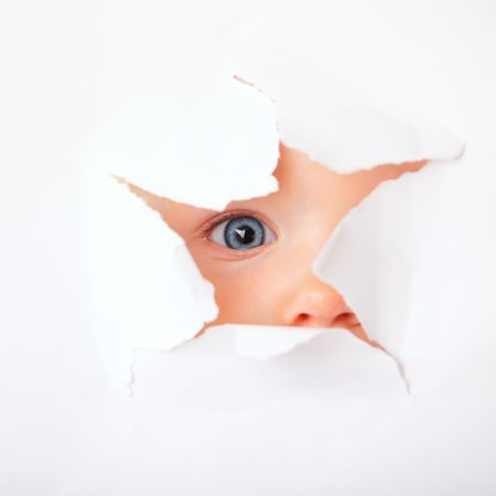 Cute baby girl looking through paper hole Stock Photo - 4954421