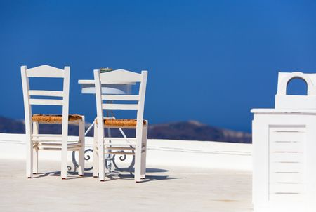 White chairs and table overlooking spectacular caldera surrounding beautiful island of Santorini, Greece photo