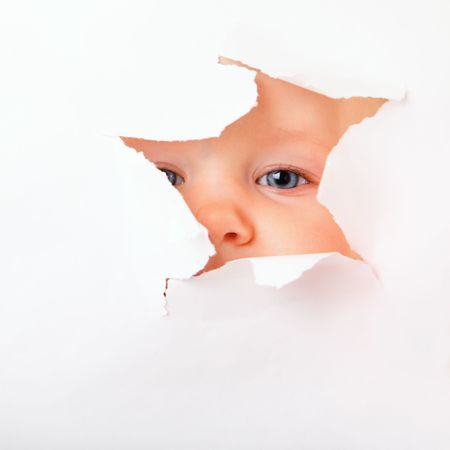 Cute baby girl looking through paper hole Stock Photo - 5012303